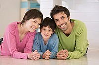 Parents and son smiling for the camera, lying on floor