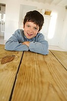 Little boy smiling for the camera, resting on table