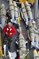A U.S. Navy Sailor stands watch over ordnance positioned on the flight deck of USS Kitty Hawk (CV 63) during flight operations June 15, 2006. Kitty Ha...