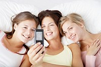 Three girlfriends using a picture phone