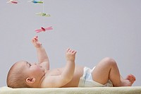 A baby playing with a mobile