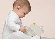 A baby looking at a book