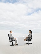 Two businesspeople in the middle of nowhere at a desk
