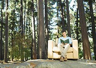 A man reading outdoors in the woods