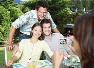 Friends enjoying an outdoor meal taking a picture