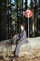 A businessman sitting by a sign in the woods
