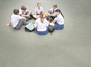 Students outside their school sitting in a circle