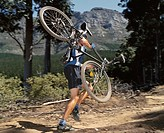 A man carrying a mountain bike on a path