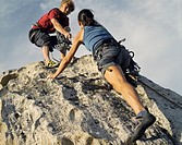 A man helping a woman climber up a mountain