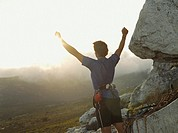 A victorious mountain climber with his arms up in the air