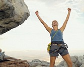 A woman climber at the top of a mountain victorious