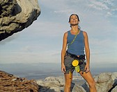 A woman climber at the top of a mountain