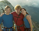 Three mountain climbers embracing