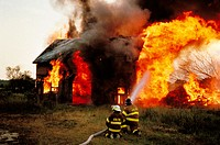 Firemen prepare to fight this barn fire which has a good head start