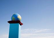 Globe on cushion on pedestal outdoors