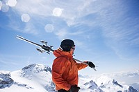 A male skier on a mountain carrying his skis