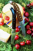 Goat´s cheese, two knives and cherries
