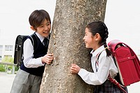 Boy and a girl next to a tree