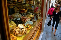 People walking past window of sweet and cake shop in Venice, Italy