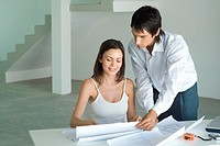 Woman sitting at table looking at blueprints, man standing, looking over shoulder