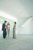 Female real estate agent standing in empty home interior with young couple, full length
