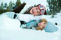 Two young friends reclining in snow, smiling at camera, one on top of the other