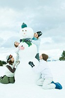 Young friends embracing snowman, smiling, full length