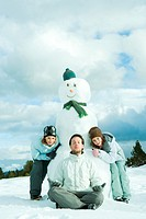 Young man meditating in front of snowman, two sisters crouching behind, smiling at camera