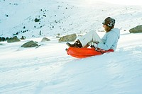 Teenage girl riding sled on ski slope, side view, full length