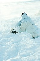Young person lying on stomach in snow, fallen, rear view