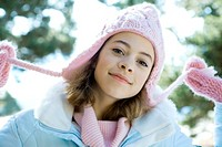 Preteen girl holding strings of knit hat, portrait