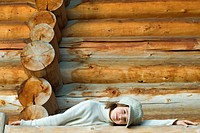 Girl leaning against railing in front of log cabin