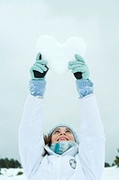 Young woman holding up heart made of snow