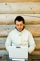 Young man using laptop next to log cabin