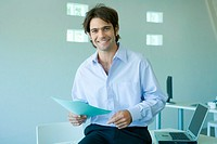 Young businessman in office, smiling at camera, waist up