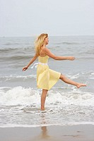 Girl having fun walking and splashing water on the beach