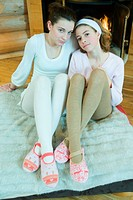Two teen girls sitting by fireplace, wearing tights and slippers, looking at camera, full length