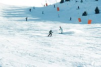 Young skiers on ski slope, in the distance