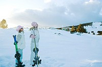 Two young friends standing together, holding skis, looking away