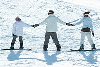 Three young snowboarders standing together, holding hands, rear view