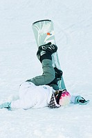 Young snowboarder lying on the ground, legs in the air, full length