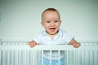 Baby standing in crib, smiling at camera