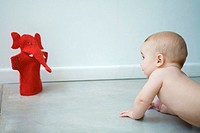 Naked baby crawling on floor, looking at puppet, waist up