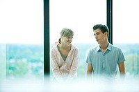 Two young friends chatting in front of window, selective focus