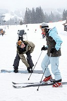 Man and woman with skis and snowboard talking at base of mountain