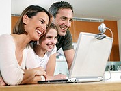 Mother Father and Daughter 9-11 Smiling at Laptop Computer