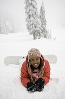 Portrait of young woman lying in snow with feet on snowboard, smiling