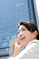 Young woman standing outdoors by skyscraper, smiling