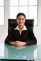 Young businesswoman sitting at desk, smiling, portrait
