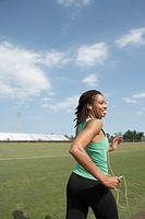 Mature woman running in stadium, using mp3 player